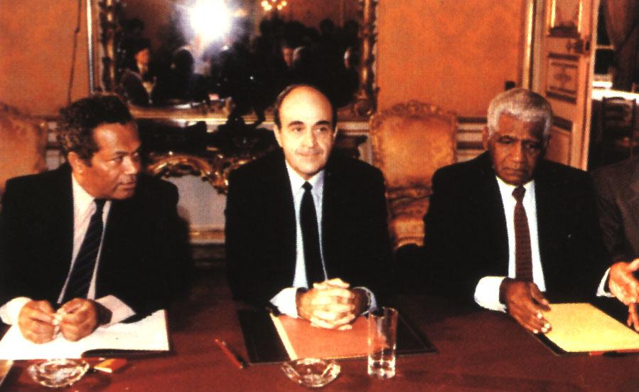 Jean-Marie Tjibaou (droite) et Jacuqes Lafleur (centre) se tiennent en face de Michel Rocard, alors Prémier ministre, lors de la signature des Accords de Matignon. Première étape d'un long processus de décolonisation ©DR