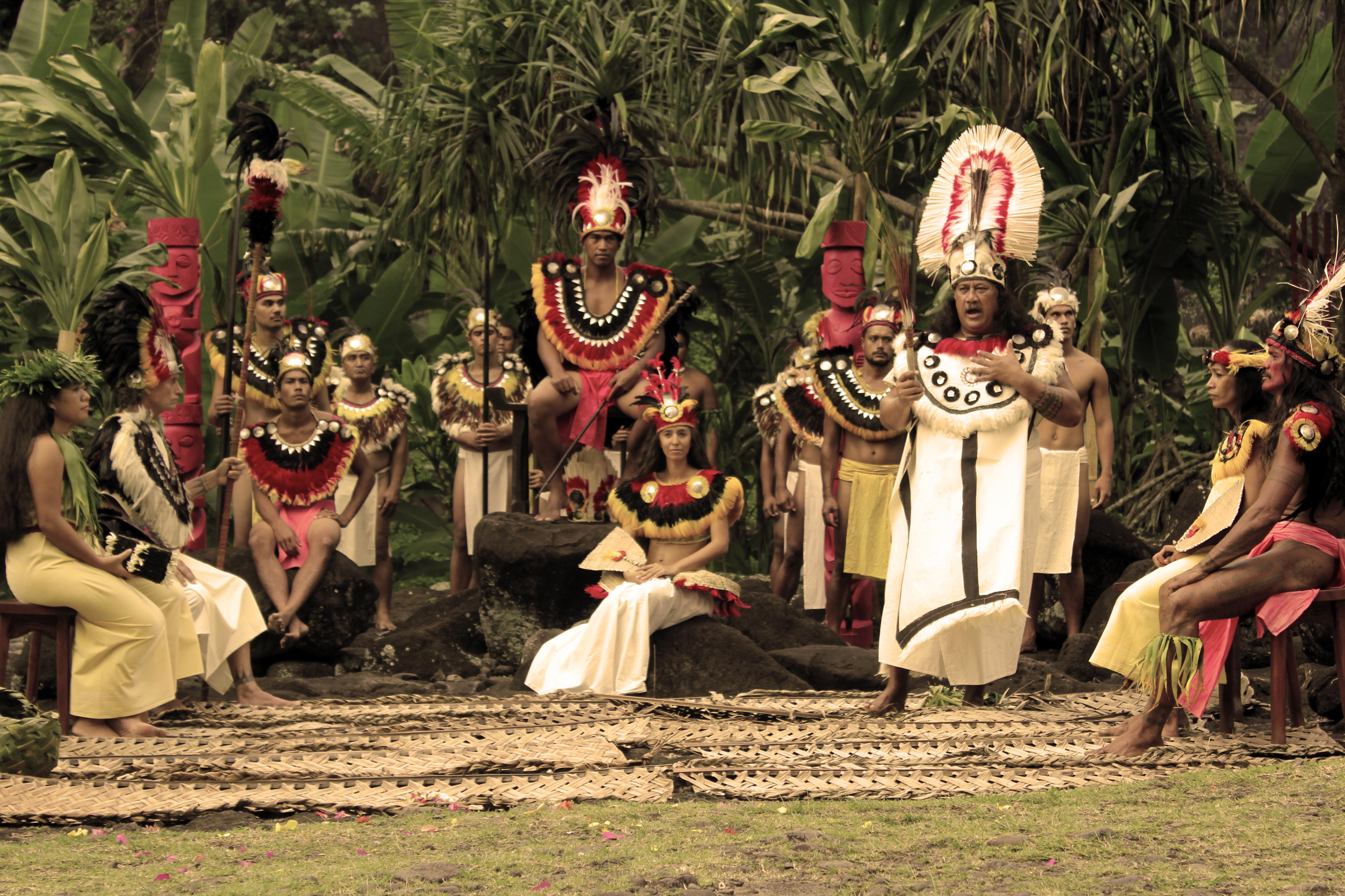 De plus en plus, les troupes de danse traditionnelle revêtissent les grands évènements politiques et religieux qui régissaient la Polynésie ancestrale, en respectant scrupuleusement les us et coutumes de l'époque, jusqu'aux classes sociales. Ici, le arii rahi, assis au fond, la reine, assise devant lui et le rassira, le prêtre en plein orero (déclamation orale). Troupe : O Tahiti E. Spectacle : Tahiti 'A Mai ©Tenahe Faatau