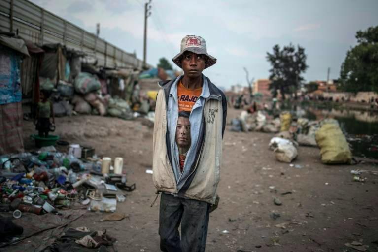 Un homme portant un T-shirt à l'effigie de l'un des candidats à la présidentielle malgache, Andry Rajoelina, marche au milieu des déchets dans un quartier d'Antananarivo, le 2 novembre 2018 ©AFP / MARCO LONGARI
